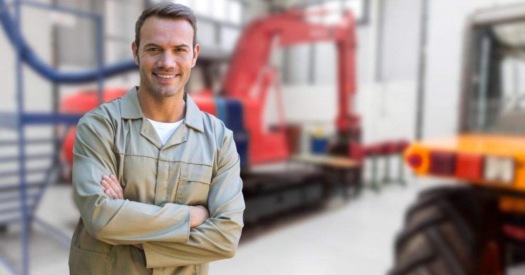 Digital composition of a confident man standing with arms crossed in factory